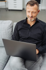 Man using a laptop on a sofa at home