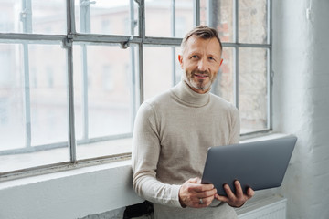 Man holding an open laptop looking at the camera