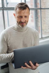 Middle-aged man working on a handheld laptop