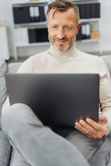 Man sitting relaxing at home with his laptop
