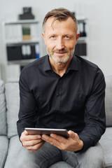 Portrait of a confident man holding a tablet PC