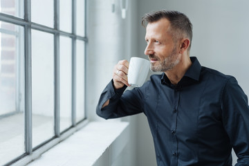 Man daydreaming while drinking coffee at work