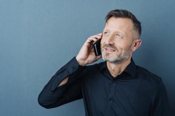 Man smiling while talking on mobile phone