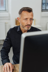 Concerned businessman staring at his monitor