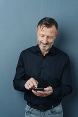 Smiling man typing a text message on a phone