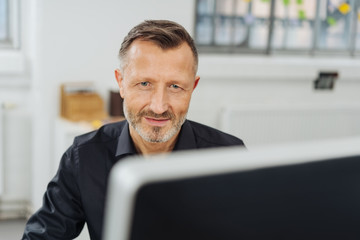 Businessman glancing over the top of his monitor