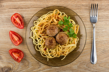 Pasta with ketchup, meatballs and parsley in plate, tomatoes