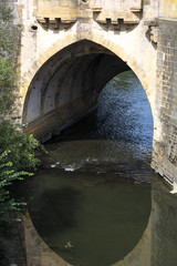 An arch of an old french bridge over the river in the summer day