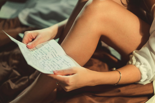 A woman in bed reading love letters