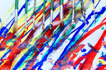 Paint brushes on a colorful background