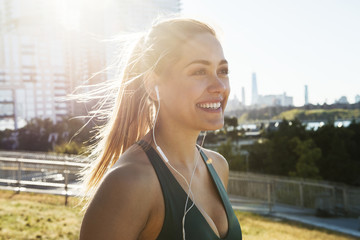 Cheerful young woman wearing sports bra while listening music against buildings in city