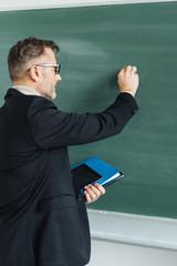 Male teacher writing on a blank chalkboard
