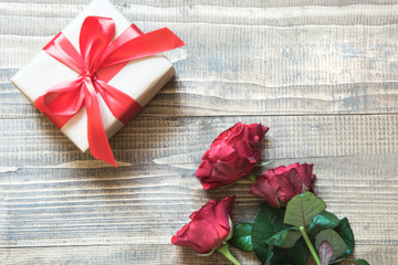 Valentine's day background with gift and red roses. View from above. Copy space. Flat lay. Mother day.