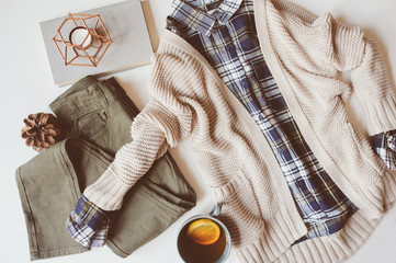 cozy autumn woman casual outfit set flat lay. Plaid shirt, knitted sweater, blue cross body bag  and khaki pants on white background. Stylish fashion, top view.