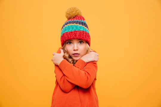 Young girl in sweater and hat having cold