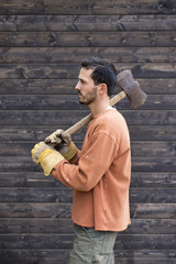 Side view of man holding axe while standing against cabin