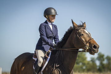 Woman riding a bay hunter jumper gelding