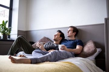 Young male couple relaxing with coffee in bed