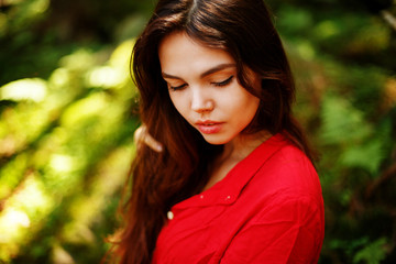 Portrait of romantic woman in fairy forest. Young woman in red dress sitting in the woods
