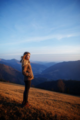 Happy young blonde woman portrait. Beauty in Nature. Young woman hiker hiking on mountain trail. Travel concept. Happy traveler standing on top of a mountain and enjoying sunset view