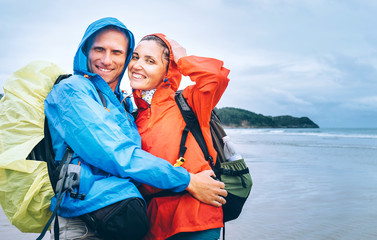 Happy smiling travelers couple in rainy day on the ocean beach