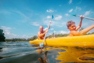Father and son are sailing in the canoe in tropical lagoon