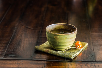 A green tea cup on rustic wood table.