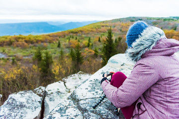 Sitting young woman photographer with camera and tripod on cold autumn morning in jacket coat, wool hat in Bear Rocks, West Virginia taking pictures of sunrise, view