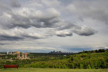 View of downtown Calgary from Edworthy park, early spring, cloudy sky, bench in the foreground