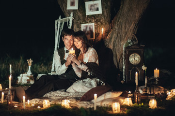 pretty caucasian engaged couple hugging beside tree with lantern