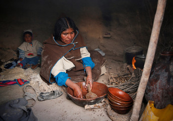 A woman washes the kitchenware at her hut in Chipaya