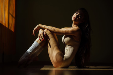 Beautiful modern ballet dancer with perfect body sits on the floor in the studio hall.