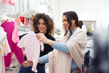 Happy pregnant woman shopping in baby store