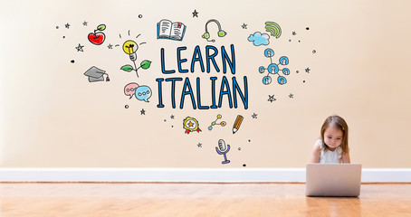 Learn Italian text with little girl using a laptop computer on floor