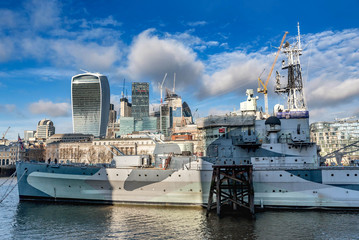 HMS Belfast warship and a  view across the River Thames with the financial skyscrapers of the city of London, UK