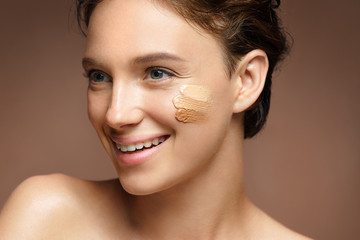 Beautiful woman with tone cream lines on her face. Photo of smiling brunette woman with perfect makeup on brown background. Skin care concept