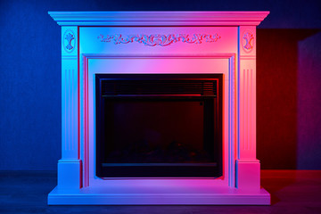 Black electric fireplace with white portal lit in red and blue lights
