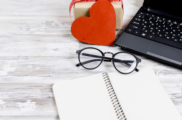 laptop, notebook and gift with heart on wooden table