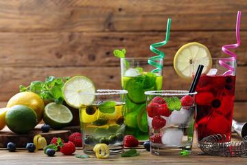 cocktail di frutta sfondo quattro bicchieri con acqua  frutti di bosco e agrumi