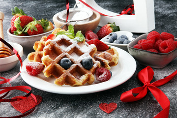 Valentine concept. Traditional belgian waffles with fresh fruit and powder sugar on wooden board