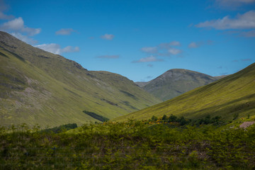 Mountain landscape in the Glencoe area in Scotland, Springtime view mountains with grassland and countryside road in the valley of the Scottish highland near Glencoe