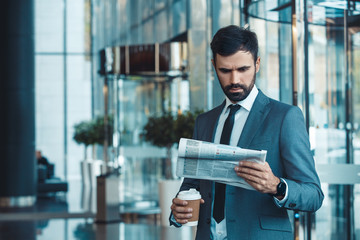 Businessman in a fromal suit in a business center morning newspaper and coffee