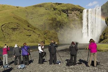 Grupo de personas fotografiando la cascada de Skógafoss, Iceland.