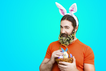 Happy Easter concept. Nice kind muscle man male with flower's beard, white ears of rabbit and basket with colorful easter eggs in orange t-shirt isolated on blue background
