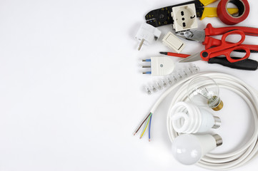 Top view of working tools and components of the electrical system on white background.