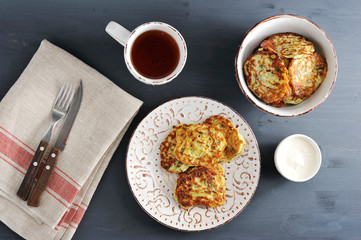fritters of zucchini with tea on rustic wooden background w