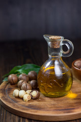 Natural macadamia oil in a glass bottle with macadamia nuts on wooden board.