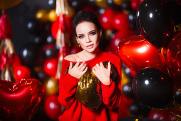 Young woman wearing red sweater and black tights holding heart. Beautiful hot female posing in sensual way in St. Valentines day interior with balloons.