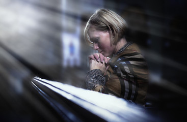 Woman praying in churches. (religion, faith, meditation concept)
