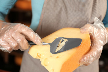 Young woman slicing delicious cheese in shop